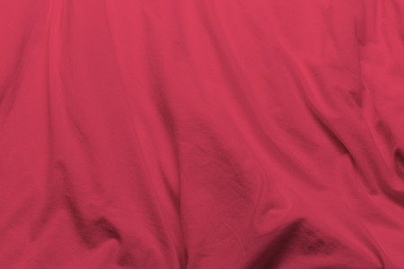 creased: creased red cloth material fragment as a background.