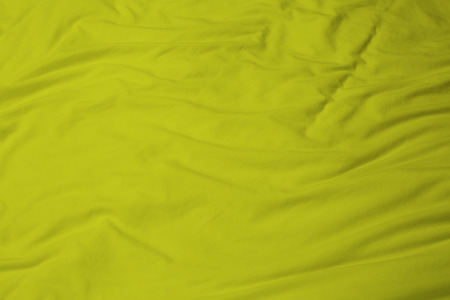 creased: creased yellow cloth material fragment as a background.