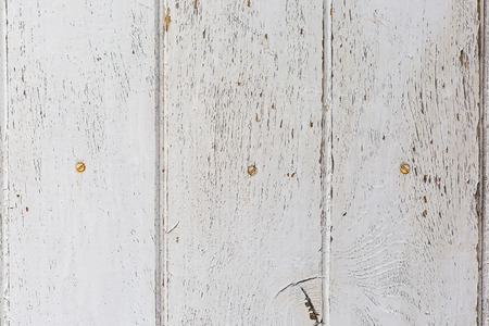 wooden background of weathered distressed rustic wood with faded white paint showing wood texture.