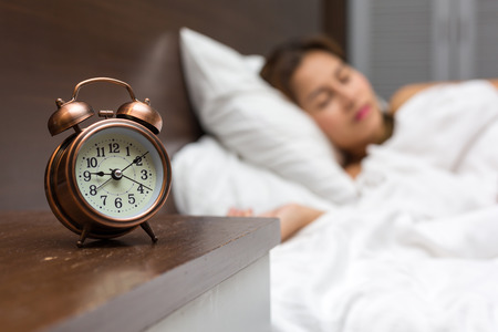 oversleep: Close up of alarm clock on table and woman sleeping in background.