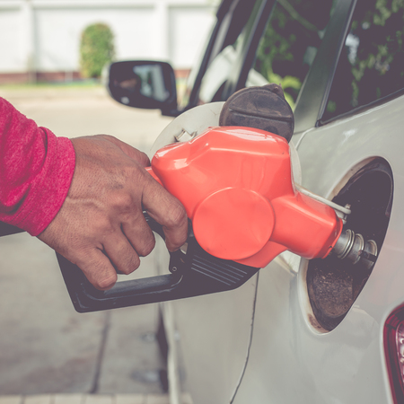 refilling: Hand holding fuel pump nozzle and refilling car.
