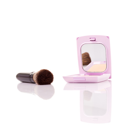 face powder: closeup of brush and face powder isolated on white