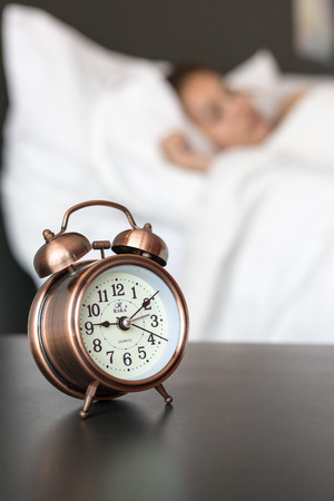 pace: Close up of alarm clock on table and woman sleeping in background.