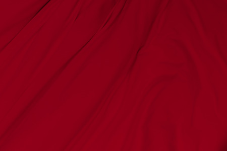 Creased red cloth material fragment as a background.