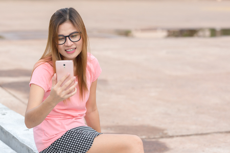 Portrait of a smiling asian woman making selfie photo on smartphone Stock Photo