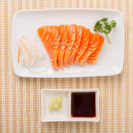 salmon sashimi slices on a black plate with sauce and wasabi,Japanese food