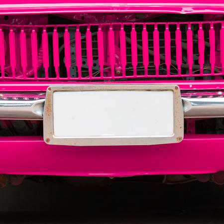 motor de carro: Primer plano de la matr�cula en el coche delante de �poca de color rosa.