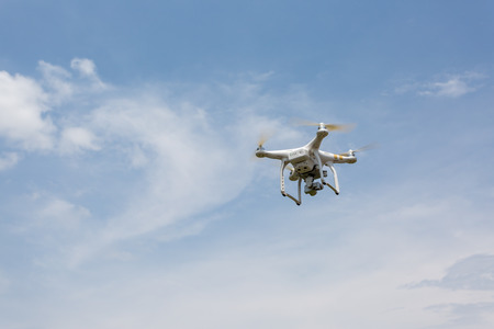 remote controlled: Udon Thani ,Thailand- MAY 18, 2016: White remote controlled Drone Dji Phantom  equipped with high resolution video camera hovering in air with clear blue sky in the background.