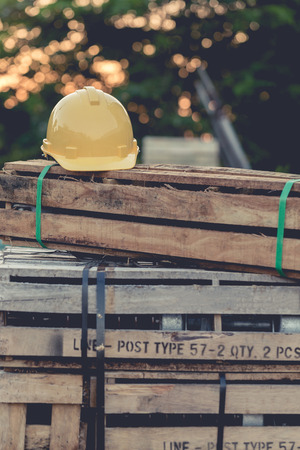 yellow helmet: Yellow helmet on wooden boxes. bokeh background with nature light