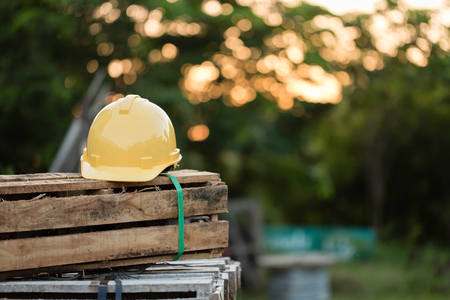 greenfield: Yellow helmet on wooden boxes. bokeh background with nature light