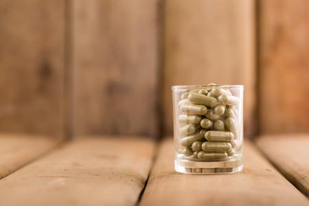 木製の背景を持つガラスのカプセルの緑ハーブ。