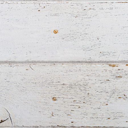 barnwood: wooden background of weathered distressed rustic wood with faded white paint showing wood texture.