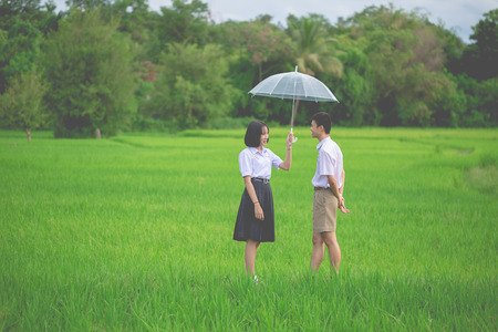 UdonThani, Thailand - Sep. 2, 2016 : Thai Students with nature rice fields in the background.