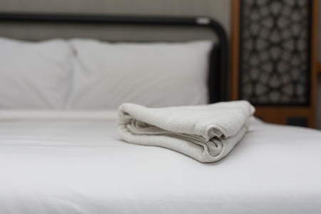 fresh white bath towels on the bed sheet. Stock Photo