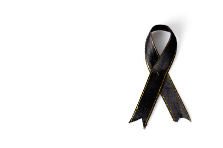 Black awareness ribbon with copy space isolated on white background. Mourning and melanoma symbol. Stock Photo
