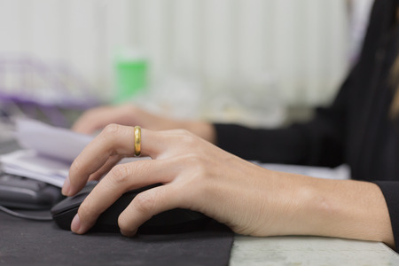 Female hand holding computer mouse for office work