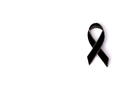 self harm: Black awareness magnet ribbon with copy space isolated on white background. Mourning and melanoma symbol.