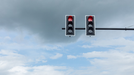 two traffic lights showing red in all directions against the blue sky with a generous copy space