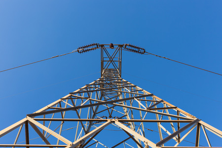 Electricity pylon silhouetted against blue sky background. High voltage tower Foto de archivo