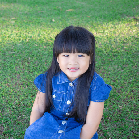 Happy little asian girl having fun at the park with space. Banco de Imagens