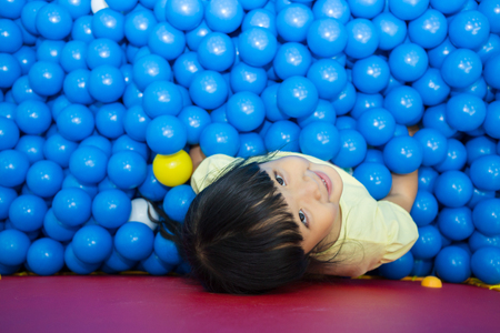 Little asian girl playing lying in colorful balls park playground.