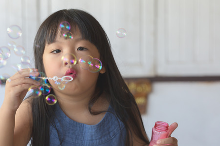 slow motion: Cute asian little girl is blowing a soap bubbles,Slow motion.