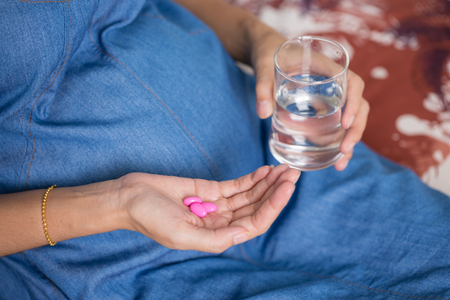 水と薬のガラスと妊娠中の女性の手のクローズ アップ