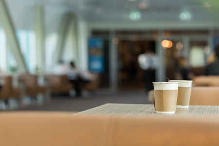fastened: Paper cups of coffee on wooden table in coffee shop with copy space. Stock Photo