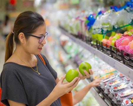 アジアの女性のスーパー マーケットで果物の買い物をしました。