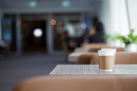 Paper cups of coffee on wooden table in coffee shop with copy space. Stock Photo
