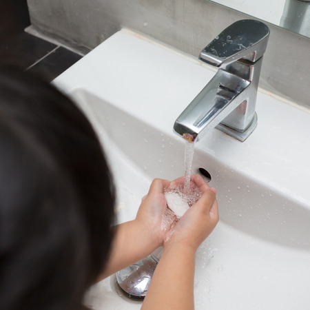 Kid washing of hands with soap under running water