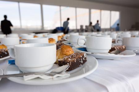 クローズ アップ コーヒーの白いカップとデザートはビジネス男背景を持つレストランで朝食の準備します。