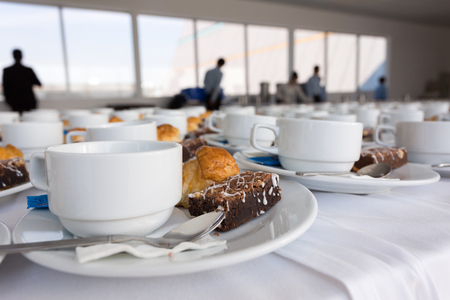 Close up coffee white cup and dessert  prepare for breakfast in restaurant with business man background.
