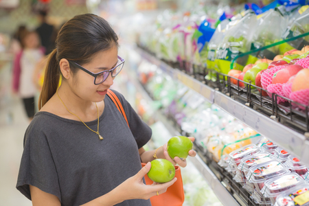 Asian women were shopping for fruits in supermarkets.