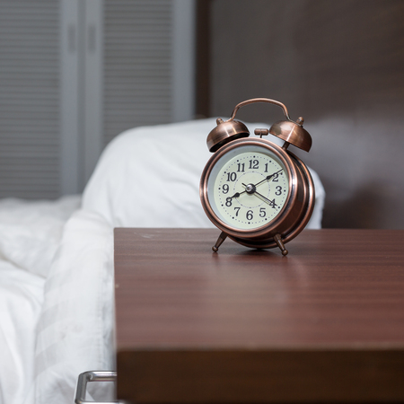 The alarm clock is placed on the bedside table Stock Photo