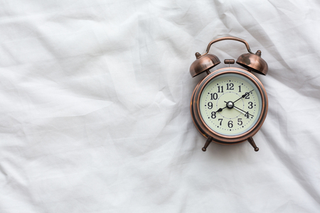 The alarm clock rests on a white bedspread