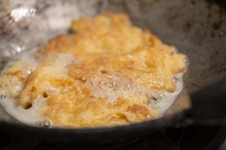 Frying omelette in a pan with hot oil. Stock Photo