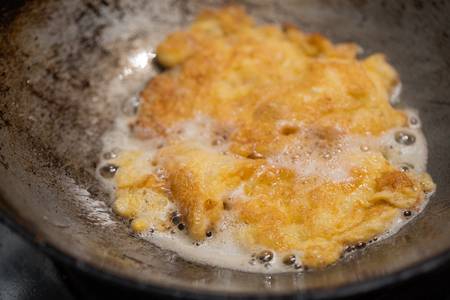Frying omelet in a pan with hot oil.