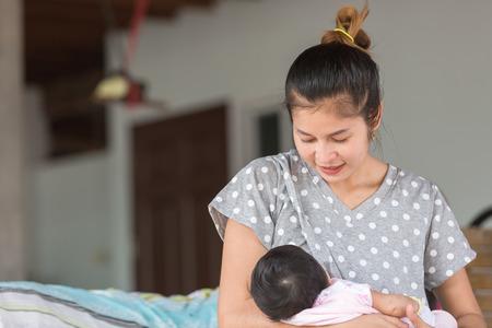 Hermosa madre feliz amamantando a su bebé.