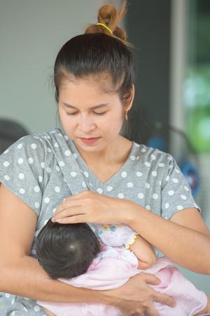 Schöne glückliche Mutter stillen ihr Baby.