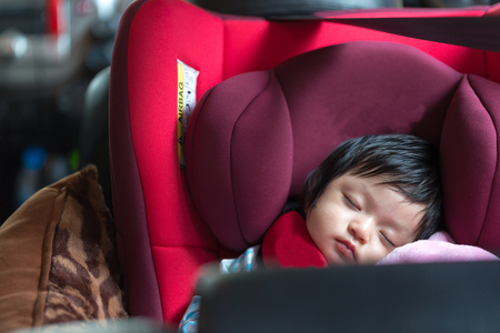 fastened: Infant sleeping in child car seat,Safe way to travel fastened seat belts in a vehicle with young kids.