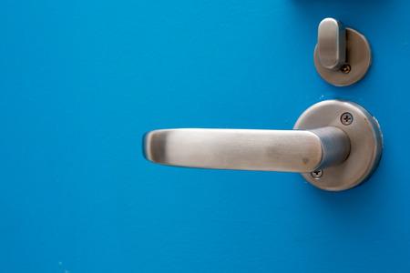 Close up of modern door handle on blue wooden door. Stock Photo