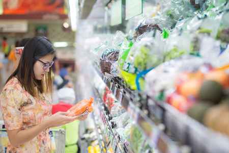 Woman in a supermarket at the shelf for fruits shopping. Stock Photo