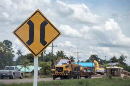 Narrow bridge sign with truck repairing bridge on the background.