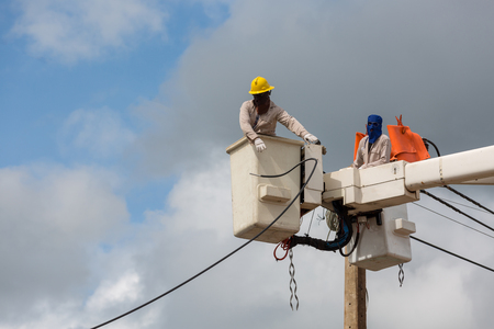 electricians repairing wire of the power line on electric power pole. Stock Photo