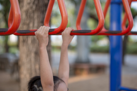 close up hands of girl playing on playground, hanging walk along the monkey bars. Stock Photo