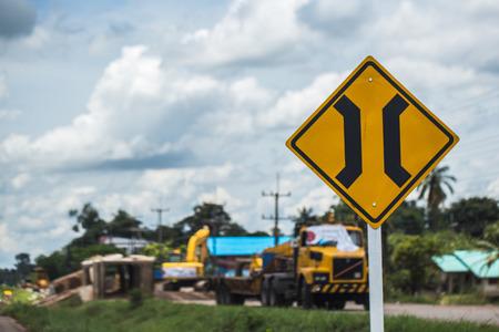 Narrow bridge sign with truck repairing bridge background.