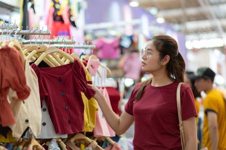 Beautiful Asian Thai girl chooses clothes in a shopping mall,Asian woman shopping choosing trying dress shop.