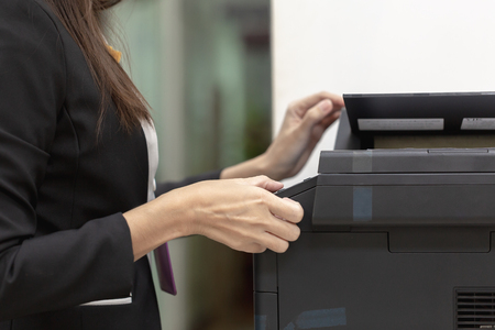 Female employees use black copy machines Imagens