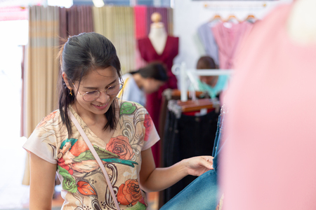 Asian woman choosing blue jeans in clothes shop.